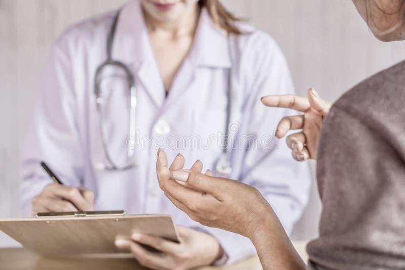 Kvinnlig patient som talar och förklarar om hälsoproblem till doktorn fotografering för bildbyråer