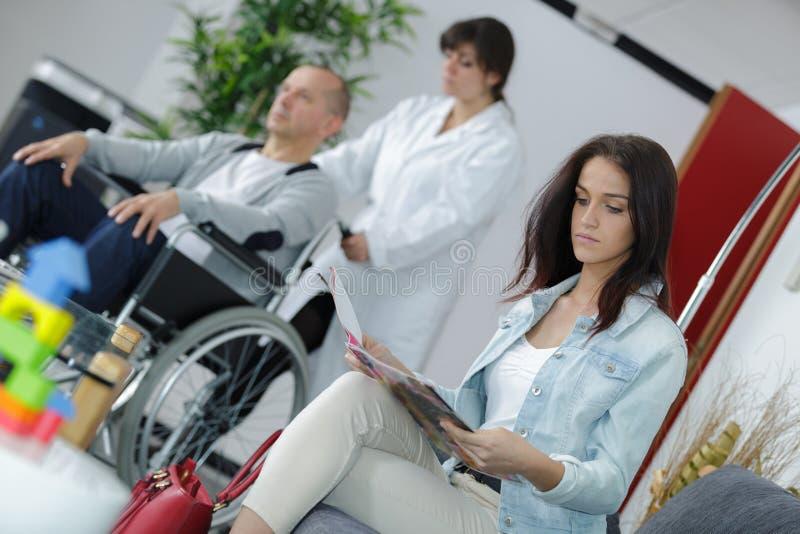 Kvinnlig patientsitting i väntande rum för doktorer arkivfoto
