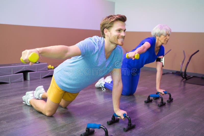 Kvinnlig pensionär med instruktören för fysisk kondition royaltyfria bilder