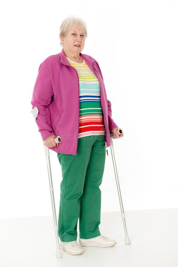 Kvinnlig pensionär med kryckor royaltyfri bild