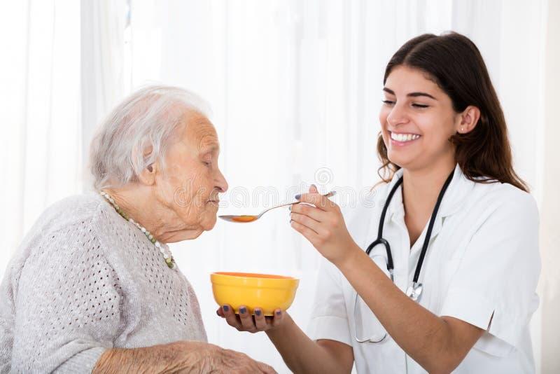 Kvinnlig pensionärpatient för doktor Feeding Soup To royaltyfria foton