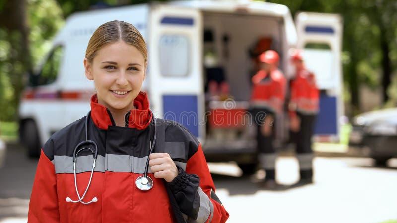 Kvinnlig person med paramedicinsk utbildning som ler in i kamera, ambulansbesättning som göras suddig på bakgrund royaltyfria foton