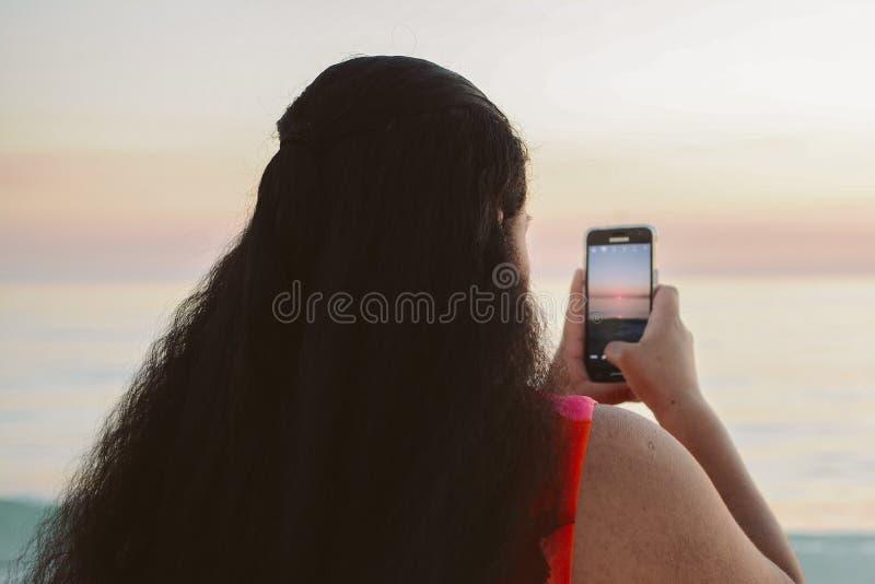 Kvinnlig person som tar mobiltelefonbilden av den härliga havhorisonten på solnedgången arkivbild