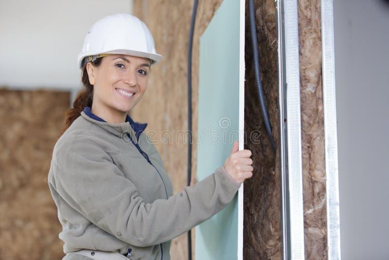 Kvinnlig platerboard för byggmästarebeslagark över den isolerade väggen royaltyfri bild