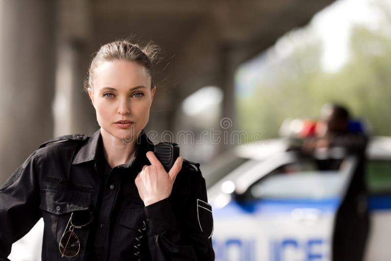 kvinnlig polis som använder walkie-talkie och ser kameran med den suddiga partnern nära bilen arkivfoto