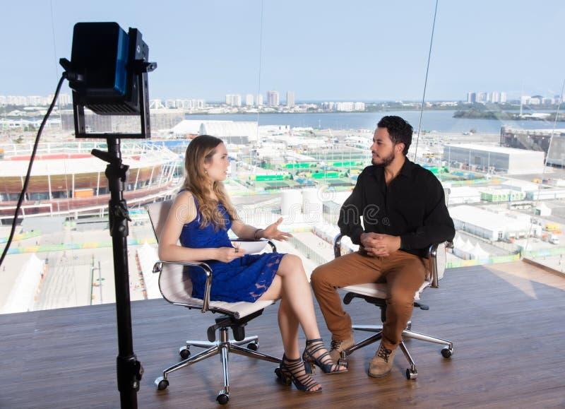 Kvinnlig presentatör som frågar en berömd kändis på tvstudion arkivbilder