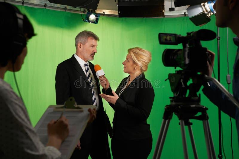 Kvinnlig presentatörInterviewing In Television studio med besättningen in arkivbild