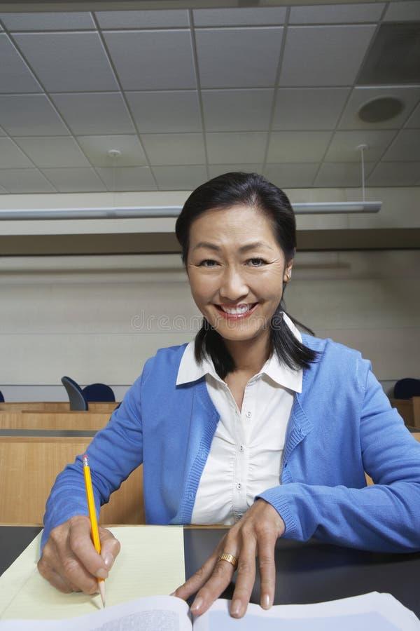Kvinnlig professor Jotting Down Notes på papper royaltyfri foto