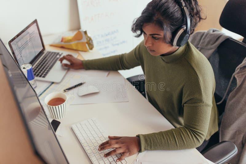 Kvinnlig programmerare som kodifierar på datoren royaltyfri bild