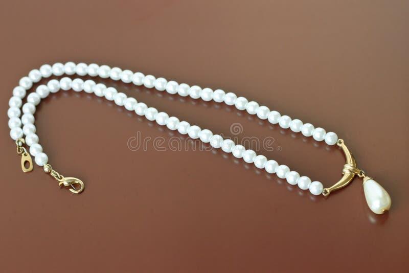 Kvinnlig prydnad: pärlor på en brun bakgrund royaltyfria foton