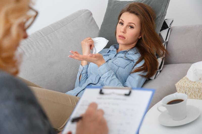 Kvinnlig psychologystterapiperiod med klienten som inomhus ligger på flickan för soffa som berättar hennes berättelse royaltyfri fotografi