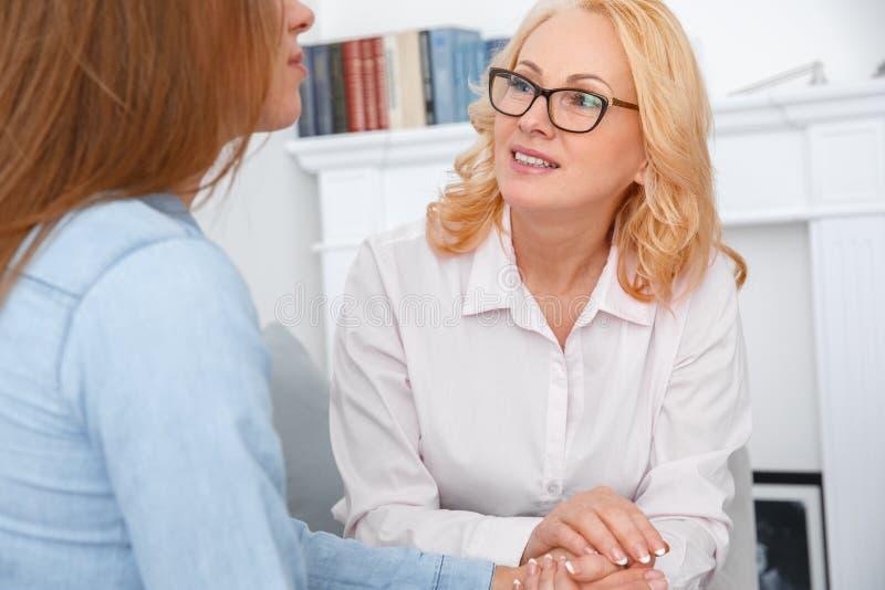 Kvinnlig psychologystterapiperiod med klienten som sitter inomhus samtal till den tålmodiga närbilden royaltyfri bild