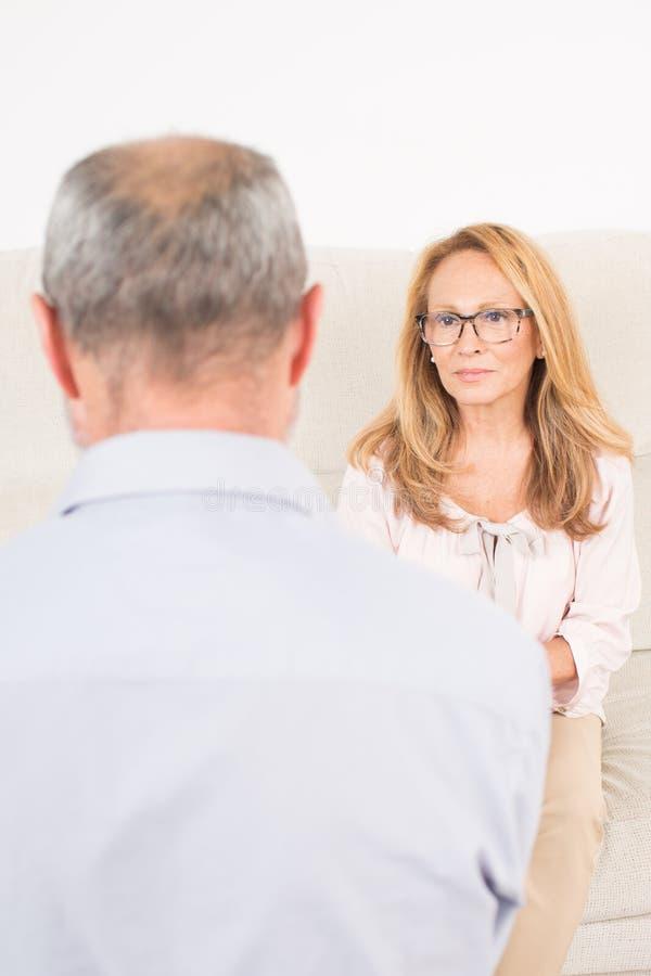 Kvinnlig psykolog som lyssnar till den äldre mannen royaltyfri bild