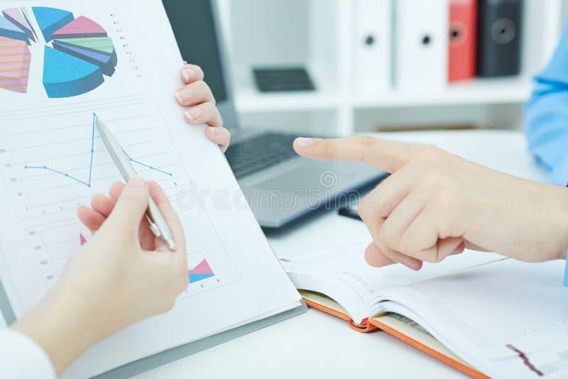 Kvinnlig punkt för penna för silver för arminnehav i den finansiella grafen som löser och diskuterar problem med kollegacloseupen royaltyfria foton