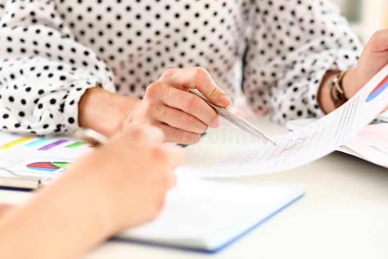 Kvinnlig punkt för penna för silver för arminnehav i finansiell graf arkivfoto