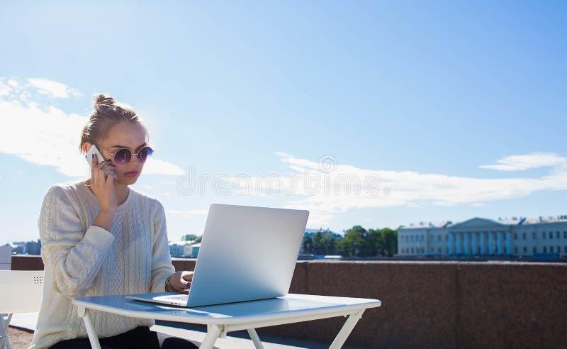 Kvinnlig rengöringsdukformgivare som har konversation på celltelefonen med klienten Kopieringsutrymme på himmel royaltyfri foto