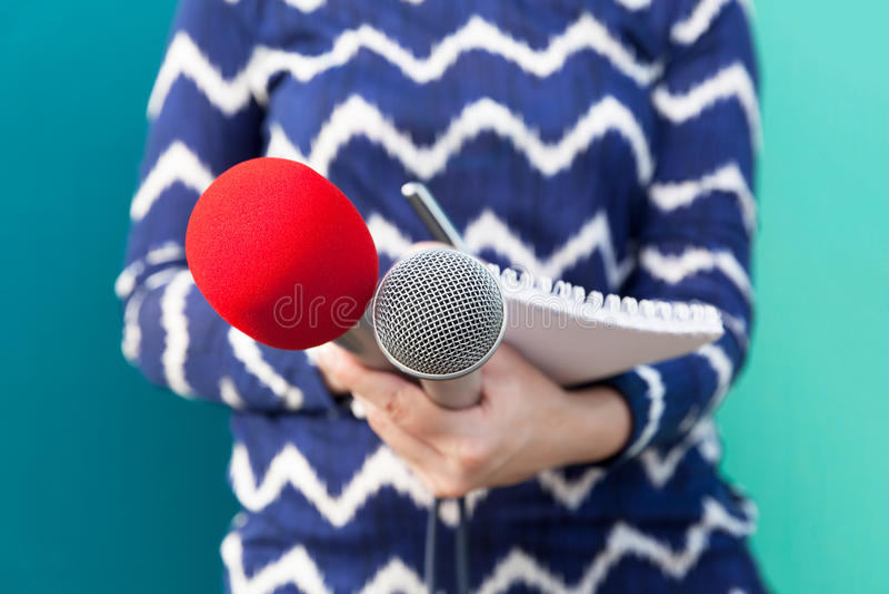 Kvinnlig reporter på presskonferensen som tar anmärkningar, hållande mikrofoner arkivbilder