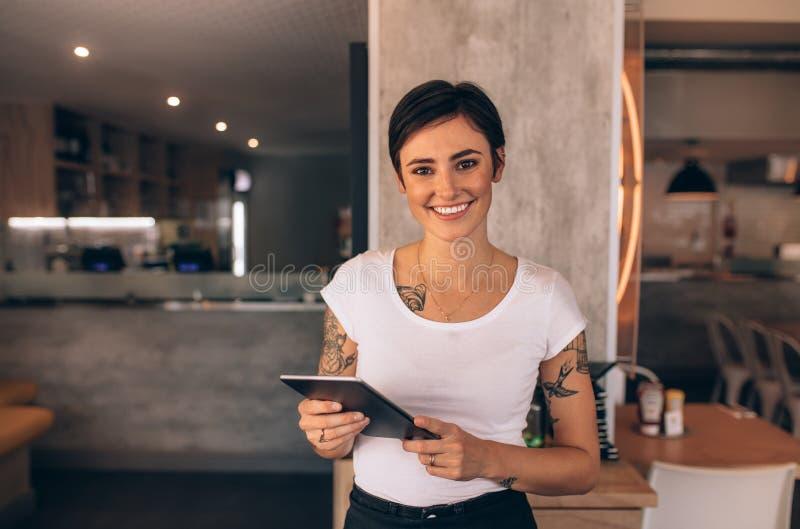 Kvinnlig restaurangägare med en digital minnestavla fotografering för bildbyråer