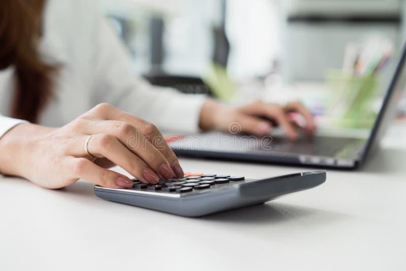 kvinnlig revisor som använder räknemaskinen och skriver på bärbara datorn arkivbild