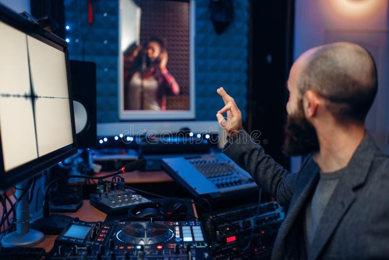 Kvinnlig sångare, i att anteckna rum och den solida teknikern royaltyfri fotografi