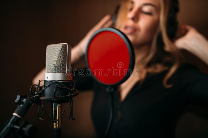Kvinnlig sångare i hörlurar mot mikrofonen arkivfoton