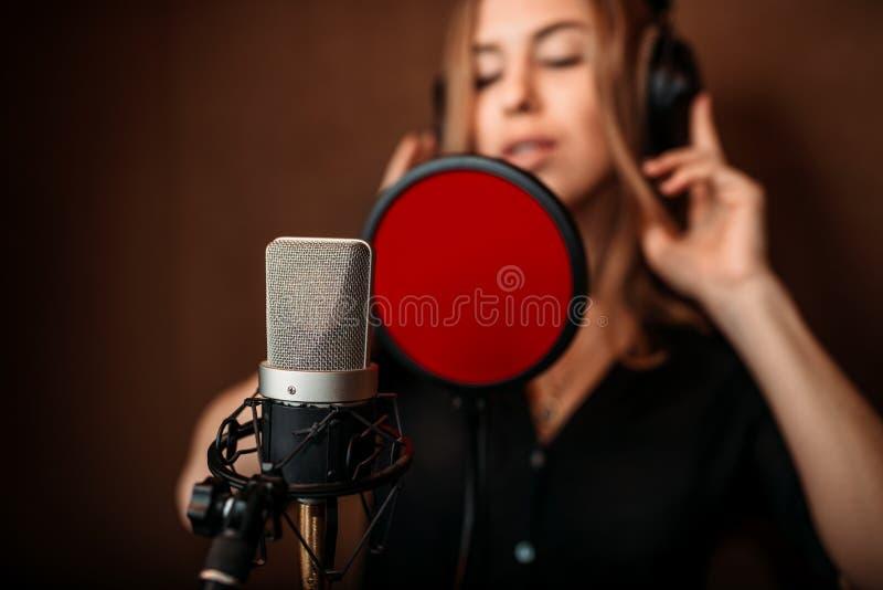 Kvinnlig sångare i hörlurar mot mikrofonen royaltyfri foto