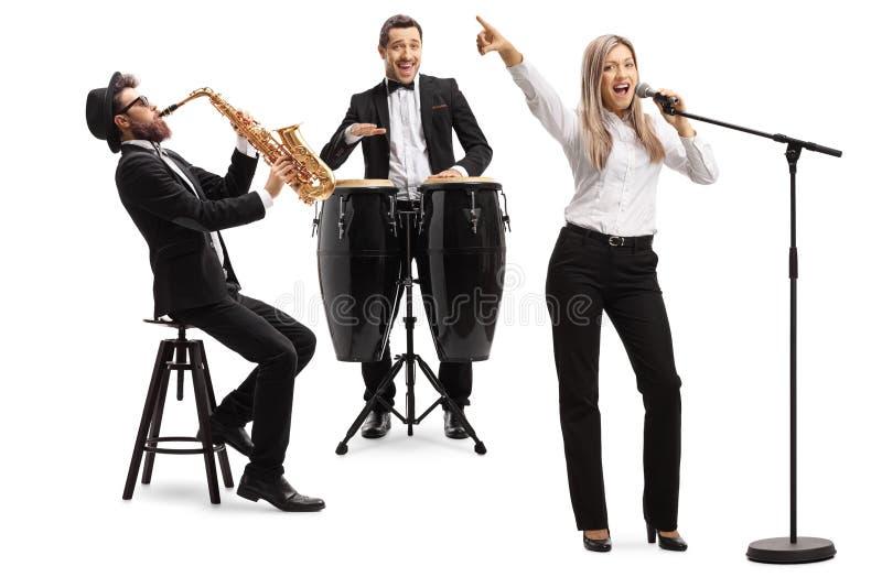 Kvinnlig sångare, man som spelar congavalsar, och man med en saxofon arkivbilder