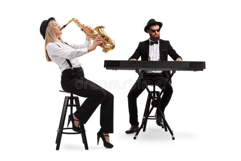Kvinnlig saxofonist och en manlig tangentbordspelare royaltyfri foto