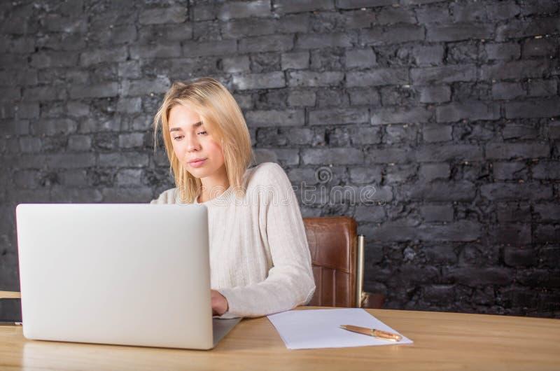 Kvinnlig sekreterare som använder netto-boken under arbetsdag i företag Hipsterflicka som använder anteckningsboken fotografering för bildbyråer