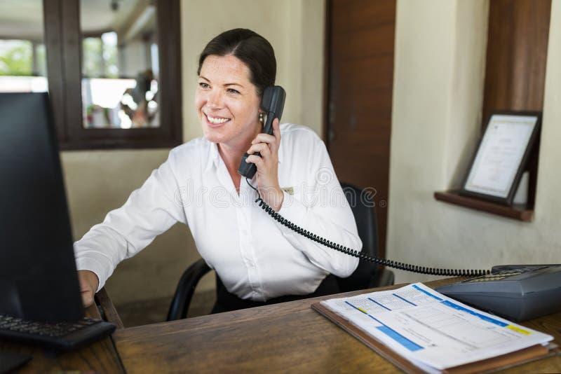 Kvinnlig semesterortreceptionist som arbetar på det främre skrivbordet royaltyfri foto