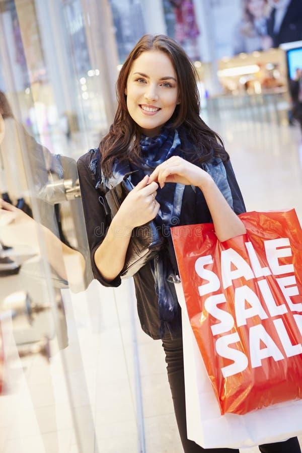 Kvinnlig shoppare med Sale påsar i shoppinggalleria arkivfoto