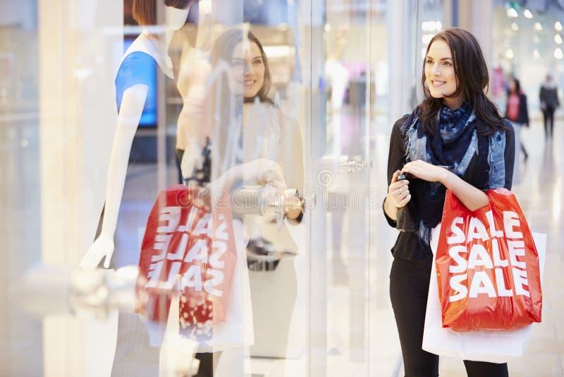 Kvinnlig shoppare med Sale påsar i shoppinggalleria royaltyfria bilder