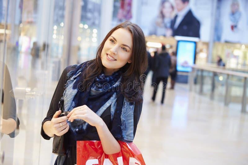 Kvinnlig shoppare med Sale påsar i shoppinggalleria arkivbilder