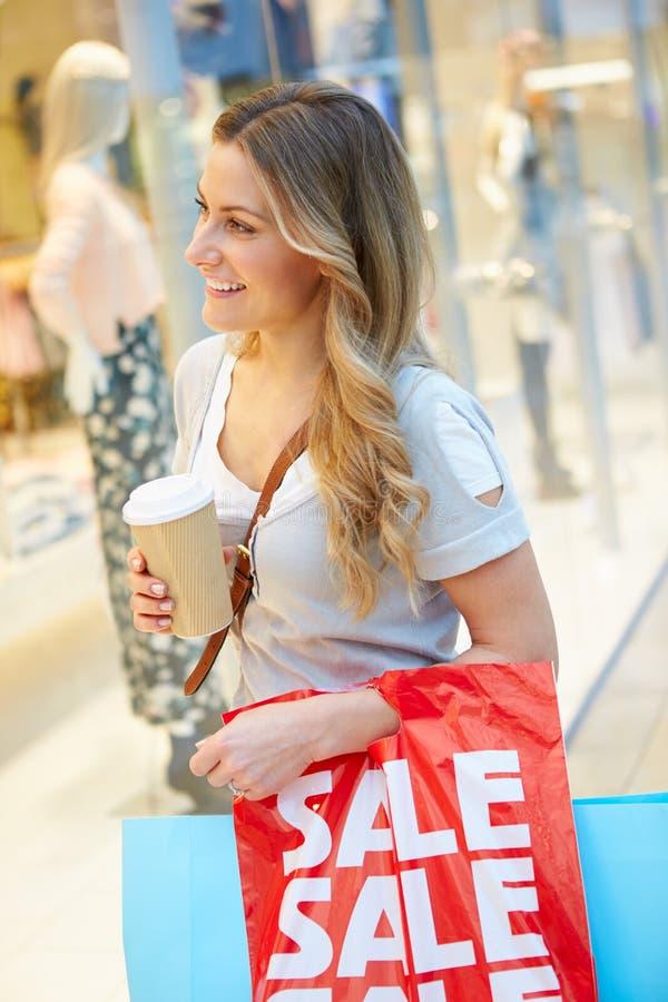 Kvinnlig shoppare med Takeaway kaffe i galleria arkivbilder