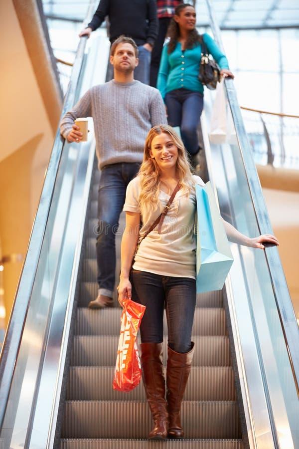 Kvinnlig shoppare på rulltrappan i shoppinggalleria fotografering för bildbyråer