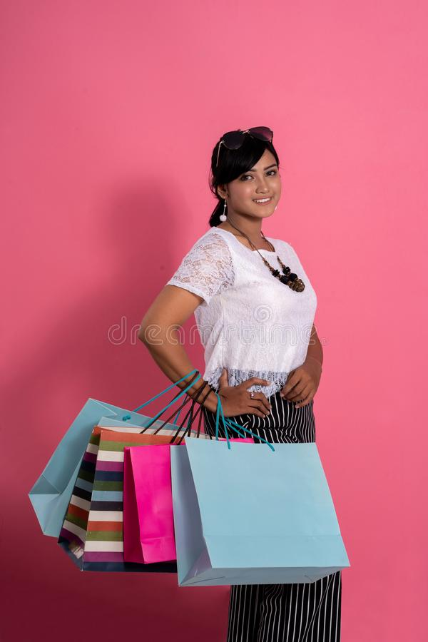 Kvinnlig shoppare som ler rymma shoppingpåsar royaltyfri foto