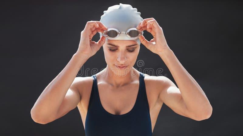 Kvinnlig simmare i en baddräkt som justerar henne skyddsglasögon arkivfoton