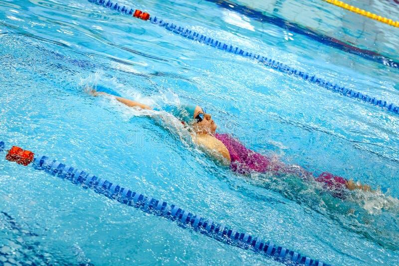 kvinnlig simmaresimningryggsim i pöl royaltyfri fotografi