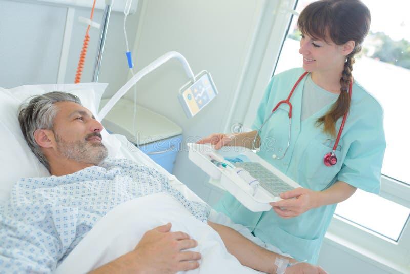 Kvinnlig sjuksköterska som att bry sig mannen på sjukhuset fotografering för bildbyråer