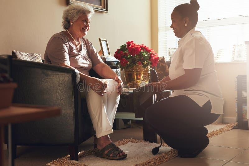 Kvinnlig sjuksköterska som besöker den höga patienten för att kontrollera blodtryck royaltyfria bilder