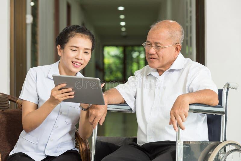 Kvinnlig sjuksköterska som diskuterar över den digitala minnestavlan med den höga mannen i rullstol arkivfoton
