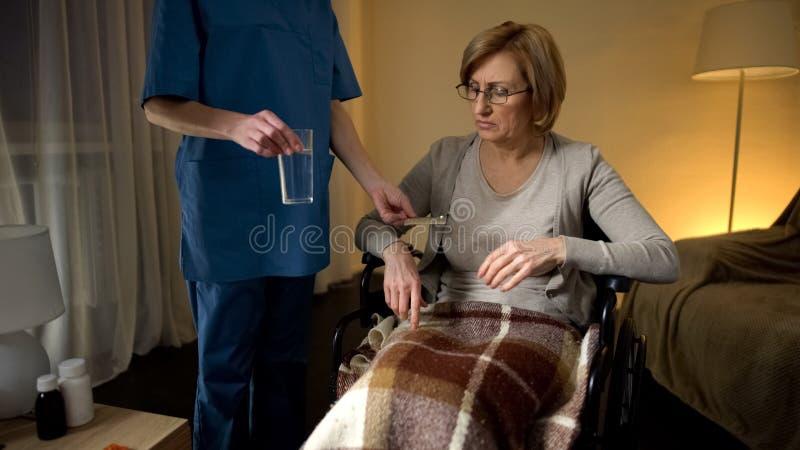 Kvinnlig sjuksköterska som ger preventivpillerar till sjukhuspatienten i rullstolen, rehabilitering arkivfoton
