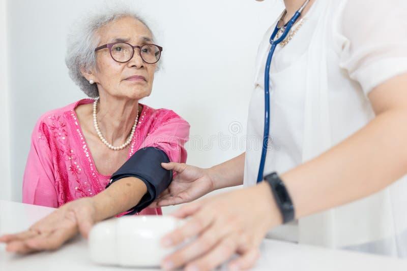 Kvinnlig sjuksköterska som hemma kontrollerar blodtryck av en hög kvinna, H royaltyfri foto