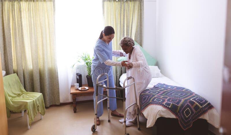 Kvinnlig sjuksköterska som hjälper den höga kvinnliga patienten att stå med fotgängaren royaltyfri foto