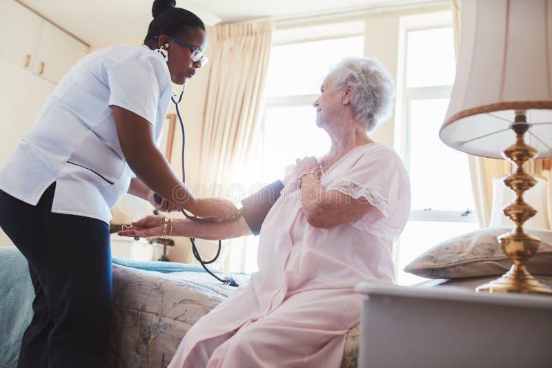 Kvinnlig sjuksköterska som kontrollerar blodtryck av en hög kvinna royaltyfri bild