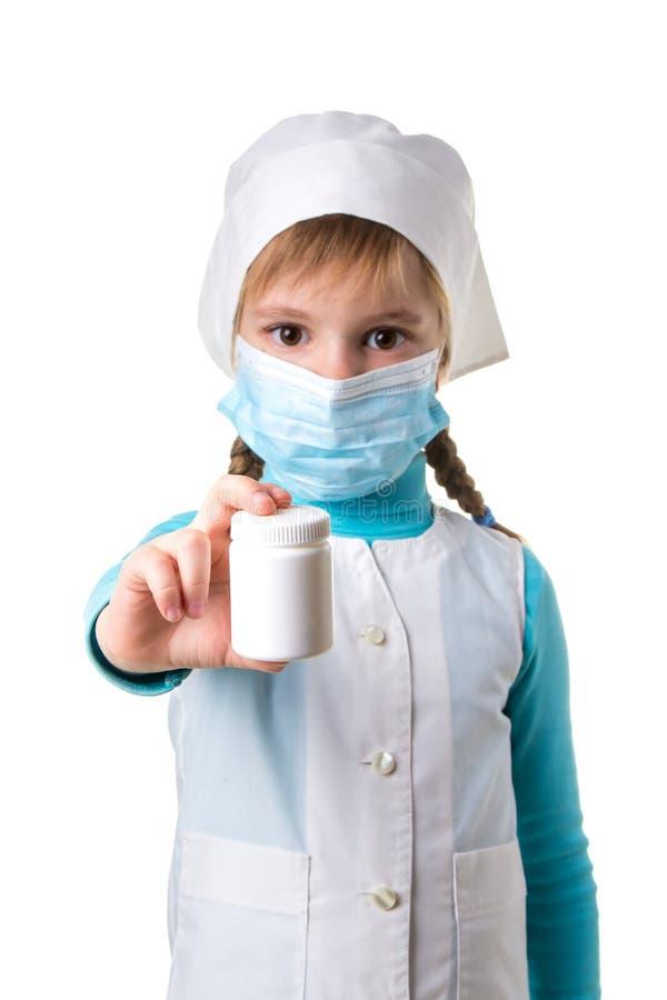 Kvinnlig sjuksköterska som pekar den vita pillerflaskan som isoleras på vit bakgrund, ståenderiktning royaltyfri foto