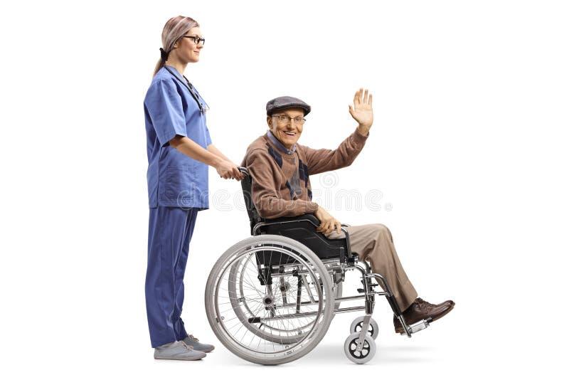 Kvinnlig sjuksk?terska som skjuter en h?g patient som sitter i en rullstol och h?lsar med handen arkivbild