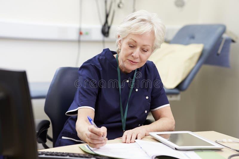 Kvinnlig sjuksköterska Working At Desk i regeringsställning royaltyfri fotografi