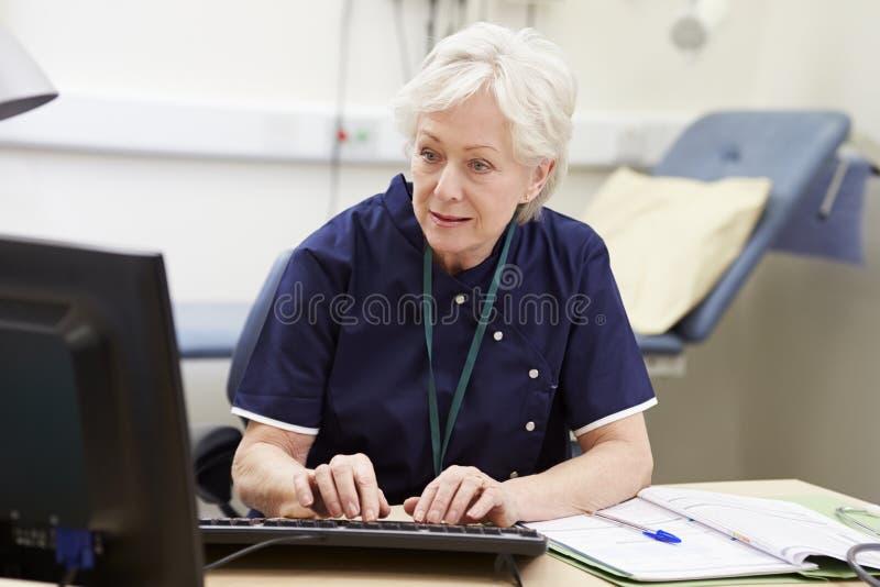 Kvinnlig sjuksköterska Working At Desk i regeringsställning arkivfoto