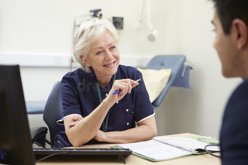 Kvinnlig sjuksköterskaMeeting With Male patient arkivfoton